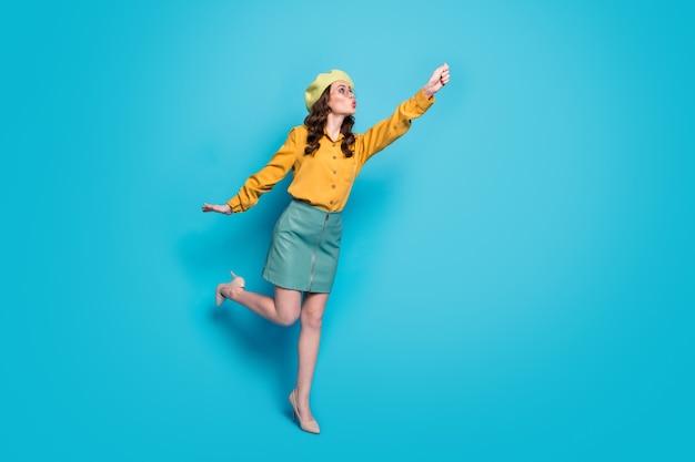 Foto de corpo inteiro de garota surpresa, segurando a mão, tente pegar ar, voar, guarda-sol, andar, usar roupas de boa aparência, sapatos isolados sobre fundo de cor azul