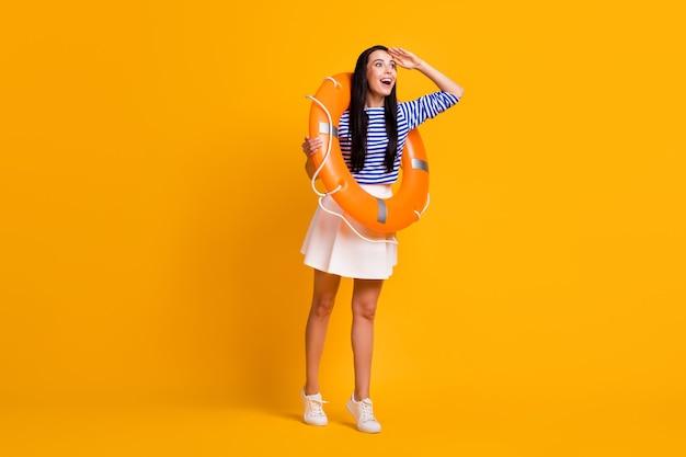 Foto de corpo inteiro de garota surpresa turista com bóia salva-vidas de borracha segurar mão olhar copyspace ver oceano usar camisa azul listrada vestido branco saia pernas isoladas brilhante brilho cor de fundo