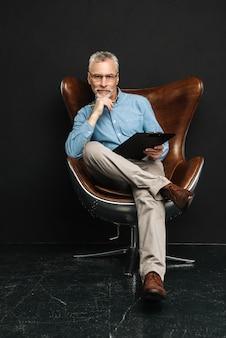 Foto de corpo inteiro de homem adulto com cabelos grisalhos, sentado na poltrona moderna e segurando a área de transferência com documentos, isolados sobre parede preta