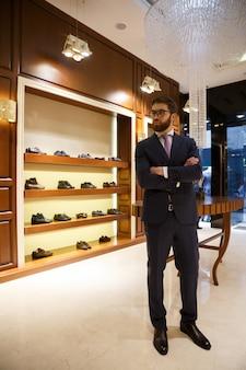 Foto de corpo inteiro de homem barbudo de terno e óculos em pé no guarda-roupa e olhando para longe