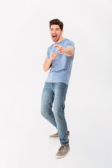 Foto de corpo inteiro de homem caucasiano em casual camiseta e calça jeans, sorrindo e apontando o dedo na câmera, significando ei, isolado sobre a parede branca