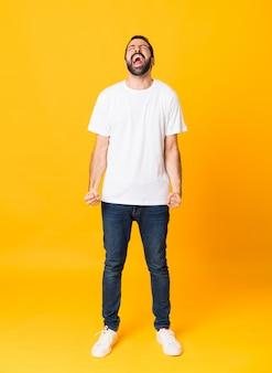 Foto de corpo inteiro de homem com barba sobre amarelo isolado gritando para a frente com a boca aberta