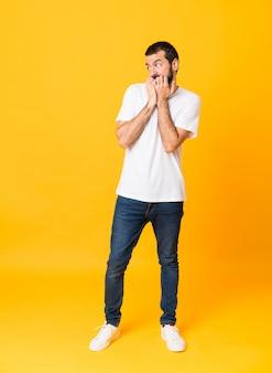 Foto de corpo inteiro de homem com barba sobre amarelo isolado nervoso e assustado, colocando as mãos na boca