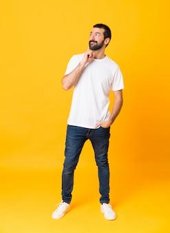 Foto de corpo inteiro de homem com barba sobre amarelo isolado, pensando uma idéia enquanto olha para cima