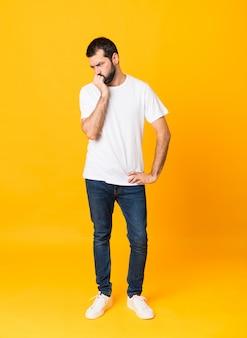 Foto de corpo inteiro de homem com barba sobre amarelo isolado tendo dúvidas