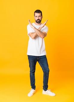 Foto de corpo inteiro de homem com barba sobre fundo amarelo isolado, sem fazer nenhum gesto