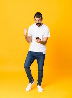 Foto de corpo inteiro de homem com barba surpreso e enviando uma mensagem