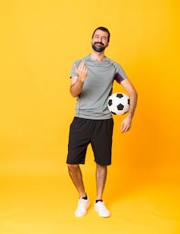 Foto de corpo inteiro de homem com bola de futebol e fazendo gesto vindo