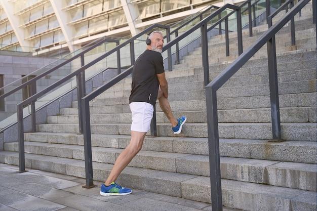 Foto de corpo inteiro de homem de meia-idade em boa forma usando roupas esportivas e fones de ouvido, ouvindo música ou podcast