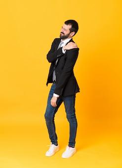 Foto de corpo inteiro de homem de negócios sobre amarelo isolado, sofrendo de dor no ombro por ter feito um esforço