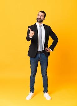 Foto de corpo inteiro de homem de negócios sobre parede amarela isolada, apertando as mãos para fechar um bom negócio