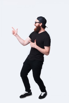 Foto de corpo inteiro de homem hipster barbudo espantado, apontando para fora sobre o branco
