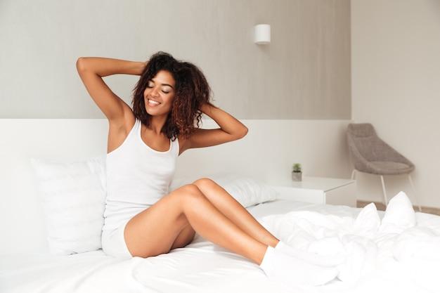 Foto de corpo inteiro de jovem alongamento na cama