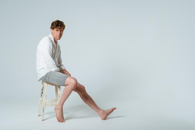 Foto de corpo inteiro de jovem bonito sentado na cadeira, vestindo camisa branca e shorts cinza