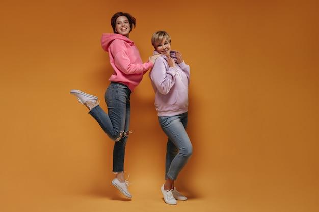 Foto de corpo inteiro de jovem com capuz rosa e jeans skinny, pulando e sorrindo junto com a velha em fundo laranja.