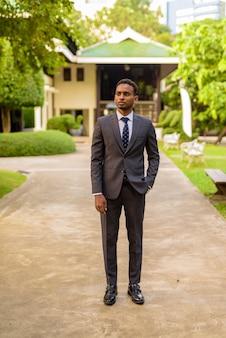 Foto de corpo inteiro de jovem empresário africano bonito ao ar livre