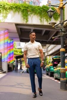 Foto de corpo inteiro de jovem empresário africano caminhando ao ar livre na estação de táxi