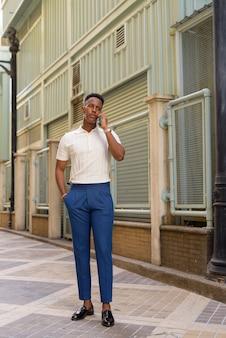 Foto de corpo inteiro de jovem empresário africano falando ao ar livre no celular