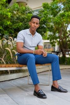Foto de corpo inteiro de jovem empresário africano sentado no banco do parque ao ar livre