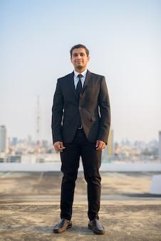 Foto de corpo inteiro de jovem empresário persa em terno contra a vista da cidade