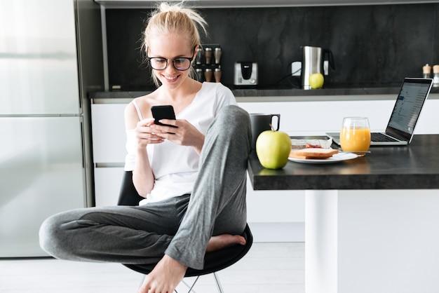 Foto de corpo inteiro de jovem focada usando smartphone enquanto está sentado na cozinha