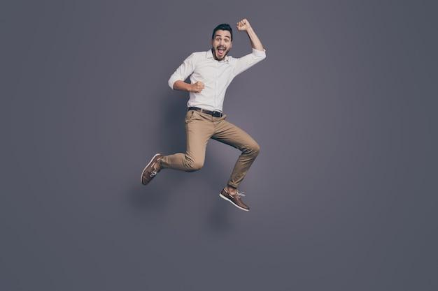Foto de corpo inteiro de jovem homem de negócios bonito pulando alto e regozijando-se