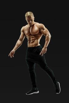 Foto de corpo inteiro de jovem sem camisa com corpo musculoso