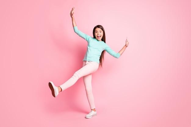 Foto de corpo inteiro de linda adorável pequena senhora latina penteado longo dança retro discoteca levantar mãos para cima pernas usar calças de moletom turquesa tênis branco isolado fundo de cor rosa