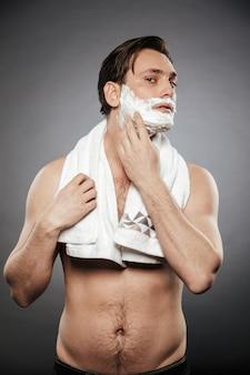 Foto de corpo inteiro de meio adulto pelado, colocando espuma de barbear no rosto com uma toalha no pescoço, isolado sobre a parede cinza