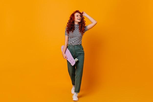 Foto de corpo inteiro de menina adolescente vermelho encaracolado com longboard nas mãos. mulher em calças jeans e camisa posando no espaço laranja.