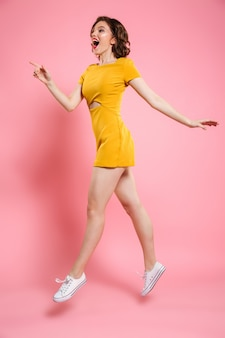 Foto de corpo inteiro de menina bonita com maquiagem de lábios vermelhos, apontando com o dedo, olhando de lado ao saltar sobre rosa