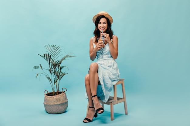 Foto de corpo inteiro de menina de chapéu, sentado na cadeira e bebendo um coquetel contra palmeira. mulher segura o copo de café nas mãos.