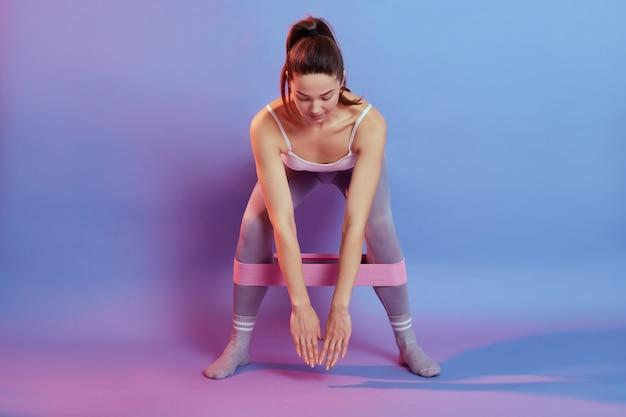 Foto de corpo inteiro de menina em roupas esportivas usando banda de resistência em suas pernas, inclina o corpo para baixo na cor de fundo, agachamento feminino, olha para baixo, treino interior.