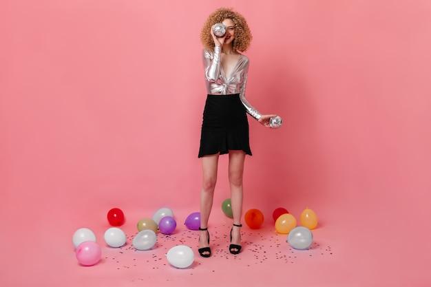 Foto de corpo inteiro de menina encaracolada com blusa prata e saia segurando bolas de discoteca no espaço rosa com balões.