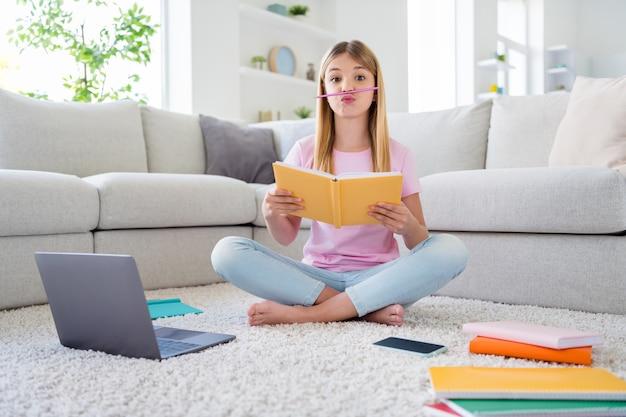 Foto de corpo inteiro de menina louca criança estudo remoto escrever redação caderno preciso descansar relaxar colocar nariz lápis careta rosto sentar chão tapete pernas cruzadas dobradas em casa dentro de casa