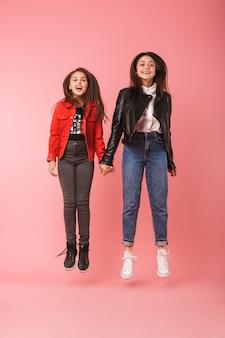 Foto de corpo inteiro de meninas divertidas em saltos casuais juntas, isolada sobre uma parede vermelha