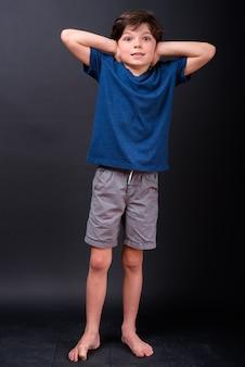 Foto de corpo inteiro de menino cobrindo as orelhas e parecendo chocado