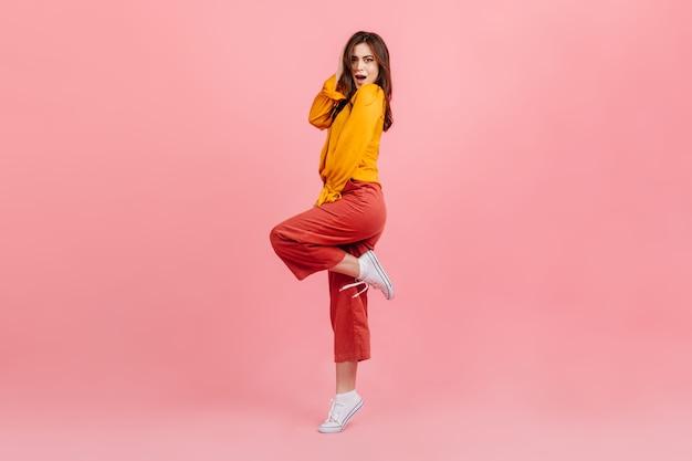 Foto de corpo inteiro de morena espantada na parede rosa. mulher de blusa e calças brilhantes levantou a perna de maneira provocante.