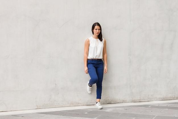 Foto de corpo inteiro de morena linda mulher jovem em pé contra a parede ao ar livre