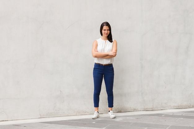 Foto de corpo inteiro de morena linda mulher jovem em pé contra a parede ao ar livre Foto Premium