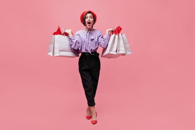 Foto de corpo inteiro de mulher de blusa roxa, calça preta e boina vermelha depois de fazer compras com sacolas nas mãos.