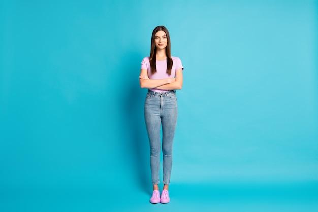 Foto de corpo inteiro de mulher doce e encantadora vestindo camiseta casual violeta calça jeans braços cruzados fundo azul isolado