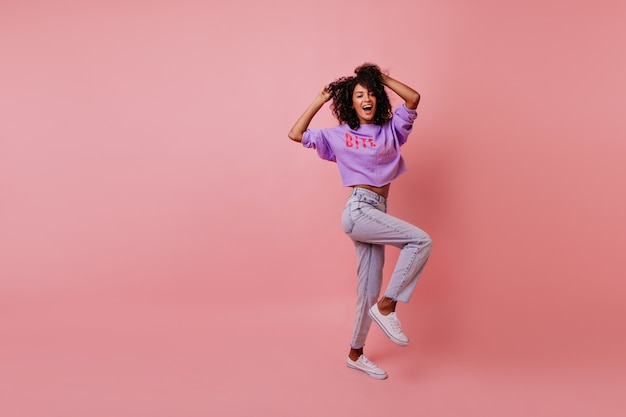 Foto de corpo inteiro de mulher elegante dançando na rosada. modelo feminino atraente em jeans brincando no estúdio.