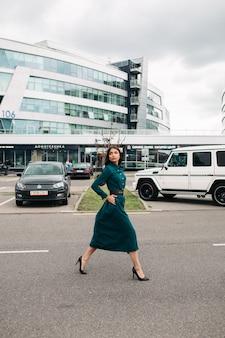Foto de corpo inteiro de mulher jovem e atraente com cabelo comprido, andando na rua da cidade, olhando para longe. estilo de vida da cidade