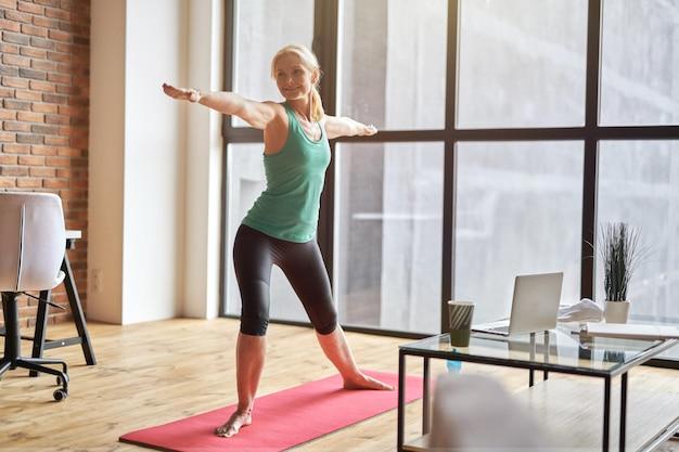 Foto de corpo inteiro de mulher madura esportiva em pose de guerreiro enquanto pratica ioga em casa em