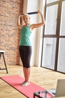 Foto de corpo inteiro de mulher madura esportiva em roupas esportivas, se exercitando com elástico em pé