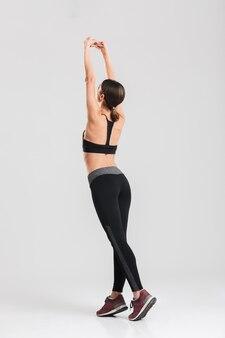 Foto de corpo inteiro de mulher magro com cabelos em rabo de cavalo, esticando o corpo e se aquecendo, isolado sobre a parede cinza