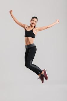 Foto de corpo inteiro de mulher saudável feliz no sportswear com abs pulando e se divertindo no ginásio, isolado contra parede cinza