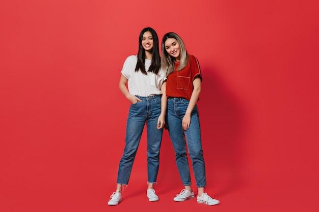 Foto de corpo inteiro de mulheres em jeans idênticos e camisetas semelhantes