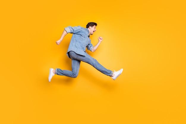 Foto de corpo inteiro de perfil lateral de corpo inteiro de alegre gritando louco homem bonito urgente para que as vendas cheguem a tempo de comprar um novo calçado branco com parede de cor vívida isolada